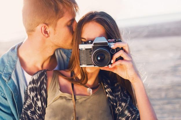 夕方のビーチ、流行に敏感な若い女の子と彼女のハンサムなボーイフレンドがレトロなフィルムカメラで写真を撮るポーズの愛のカップル。夕日の暖かい光。