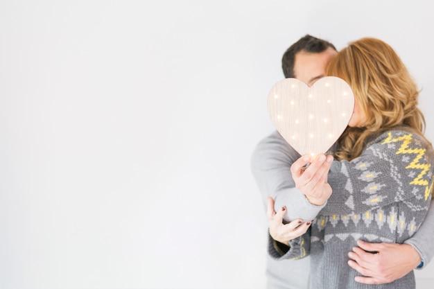 Пара в любви позирует с сердцем