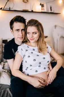 Влюбленная пара беременных обнимаются, ожидая ребенка