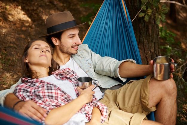 Влюбленная пара, отдыхая в гамаке в лесу