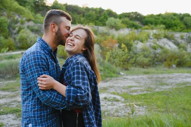 カントリーサイドの緑の丘の上に残りの愛のカップル