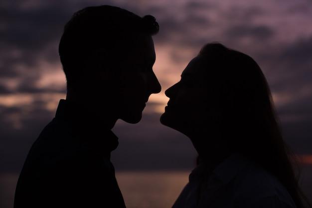 일몰 동안 사랑 실루엣 커플-코를 만지고