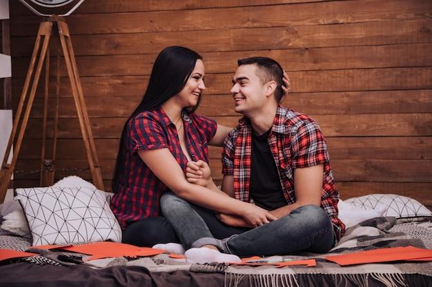 愛するカップルは、バレンタインデーにベッドと赤い紙のハートに座っています。市松模様のシャツとジーンズを着た男女がお互いを見て、スタジオでイチャイチャ。