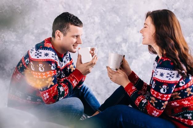Влюбленная пара сидит и пьет горячий напиток на фоне стены. отблеск от линз.
