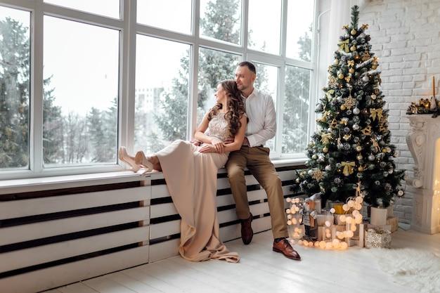 大きな窓と装飾されたスタジオのクリスマスツリーの近くに座って、抱いて愛のカップル