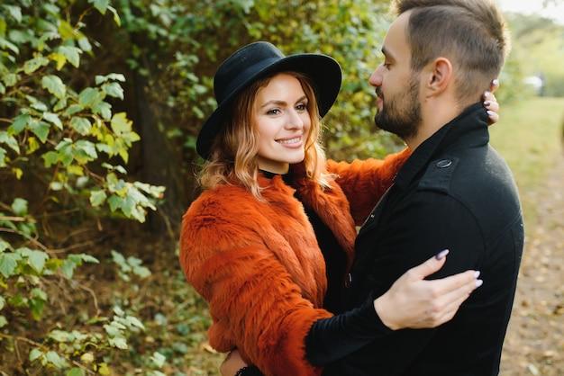 公園で秋の落ち葉に座って、美しい秋の日を楽しんでいる愛のカップル
