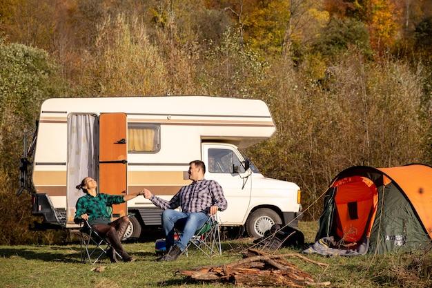 キャンプチェアに座って、美しい天気を楽しんでいる愛のカップル。ロマンチックな雰囲気