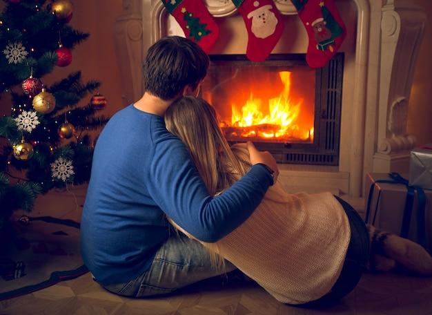 Влюбленная пара сидит на полу и смотрит на камин и украшенную елку