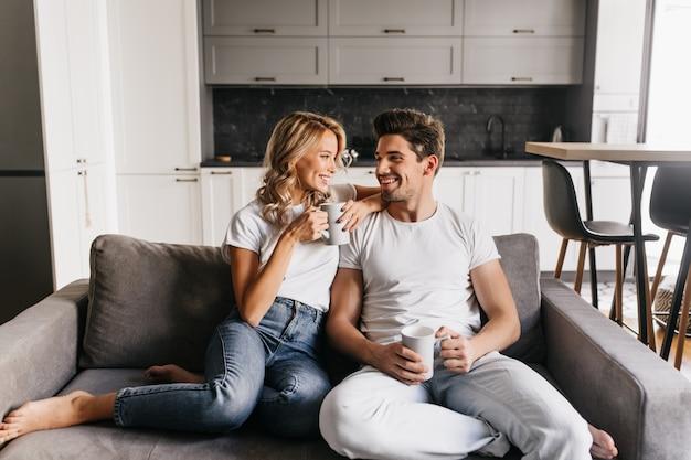 お互いを見て、笑顔でカップを保持しているソファに座っている愛のカップル。ロマンチックなカップルは家で一緒に朝を楽しんでいます。