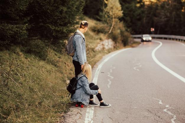 Влюбленная пара сидит на обочине дороги и смотрит на машину, которая едет на встречу.