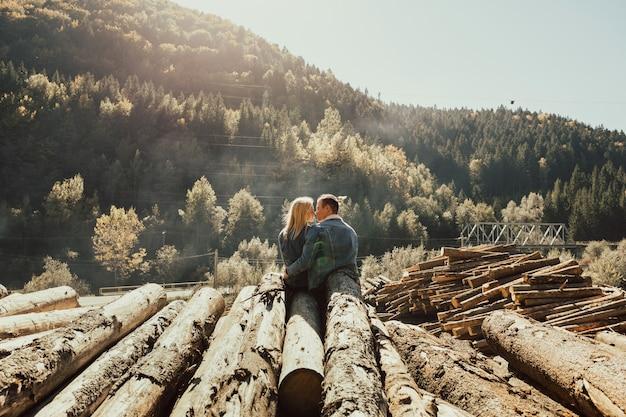 薪のスタックに座っている愛のカップル