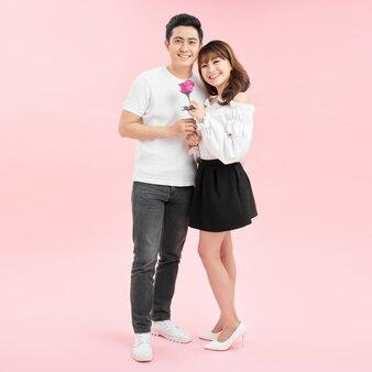 笑顔の愛のカップル。ピンクの背景の上