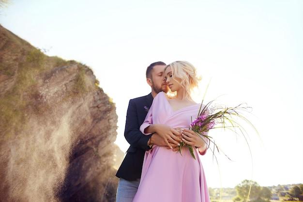 사랑에 빠진 부부는 일몰을 배경으로 물이 튀는 곳에 서 있습니다. 한 남자가 아름다운 드레스를 입은 여자를 껴안고 있습니다. 눈에 담긴 사랑
