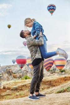 愛するカップルがカッパドキアの熱気球の上に立っています。丘の上の男性と女性は、多数の空飛ぶ気球を見ています。山のトルコカッパドキアおとぎ話の風景