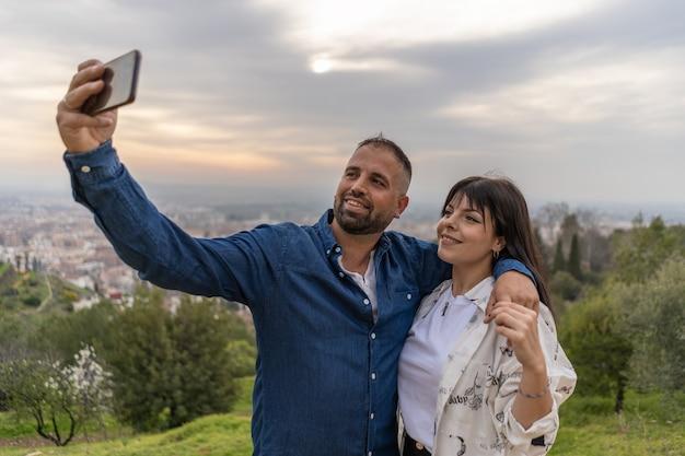 사랑에 빠진 커플은 스마트폰으로 석양에 셀카를 찍습니다.