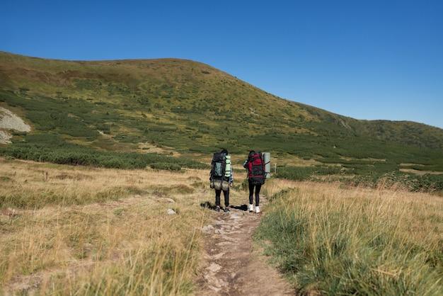 愛の観光客の男性と女性のカップルが山道を歩いています