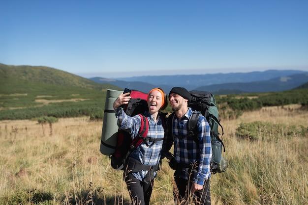 愛の観光客の男性と女性のカップルは、スマートフォンで自分撮りをしている山の平原に立っています