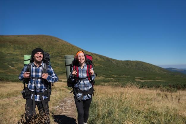 愛の観光客の男性と女性のカップルが山の平原に立つ
