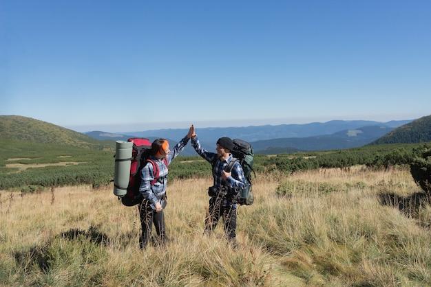 Влюбленная пара туристов мужчина и женщина стоят на равнине, поднимая ладони вверх