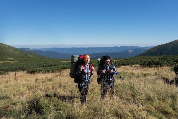 愛の観光客の男性と女性のカップルは、背中の後ろにバックパックを持って平野に立っています。