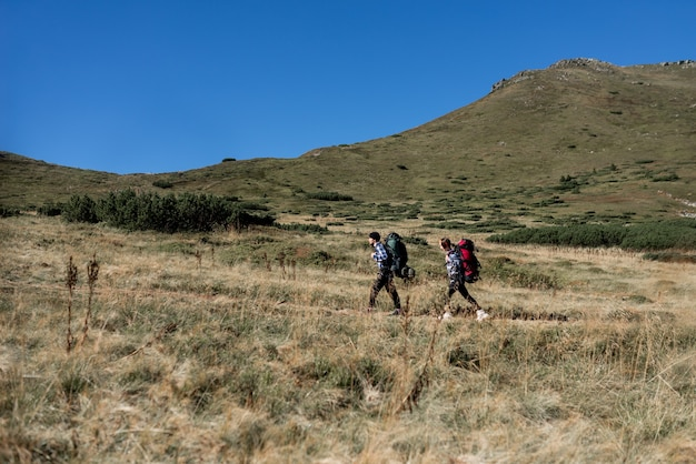 愛の観光客の男性と女性のカップルが山道を歩いて立っています