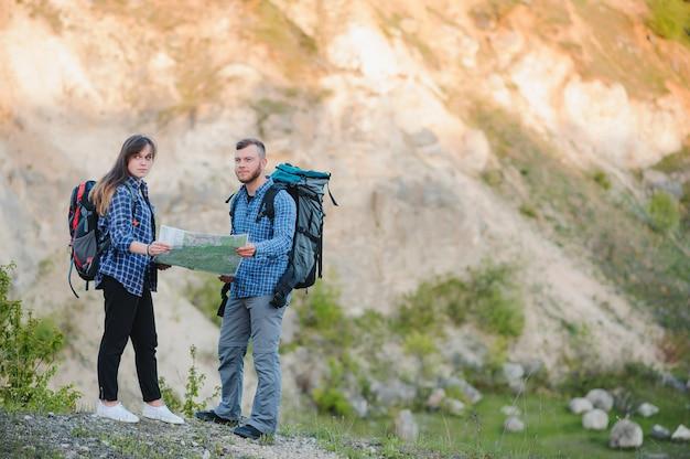 Влюбленная пара путешествует по горам с картой и биноклем