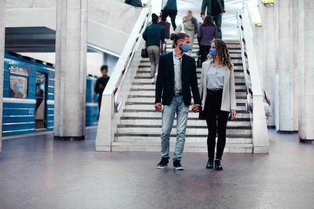 地下鉄のプラットフォームに沿って歩く愛のカップル