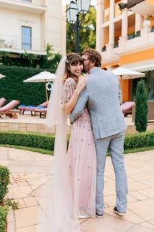 Влюбленная пара гуляет на роскошной вилле во время празднования свадьбы. полная длина.