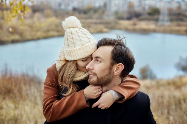 秋の公園、涼しい秋の天気を歩くのが大好きなカップル。男と女が抱き合ってキス、愛と愛情、黄色い秋の風景