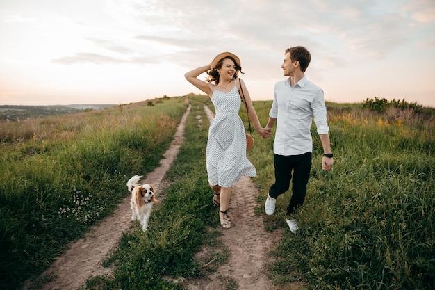 Влюбленная пара гуляет с собакой на холмах, держась за руки