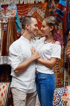 Влюбленная пара гуляет и обнимается на восточном ковровом рынке.