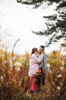 사랑에 빠진 부부는 가을 숲을 산책합니다. 남녀의 포옹과 키스, 관계와 사랑. 젊은 부부는 노란 붉은 풀밭에 서서 소녀의 손에 꽃다발을 들고 있다