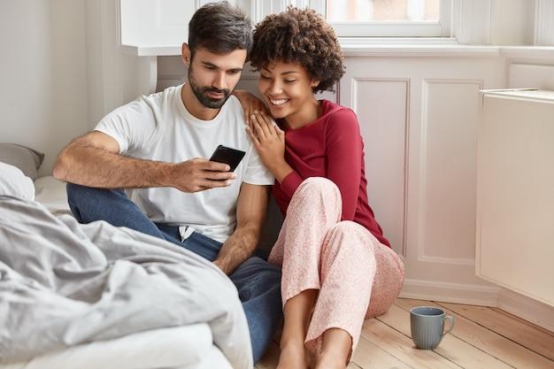 愛のカップルは携帯電話で面白いビデオを見る