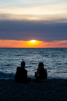 Влюбленная пара, наблюдая закат вместе на летних каникулах путешествия пляжа. люди силуэт сзади сидя, наслаждаясь видом на закат на море на тропических каникулах назначения. романтическая пара на пляже