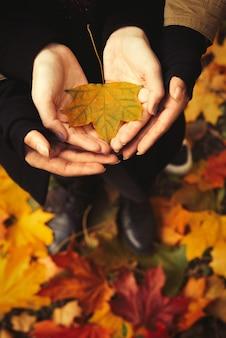 Влюбленная пара с открытыми руками, держа желтый лист в лесу