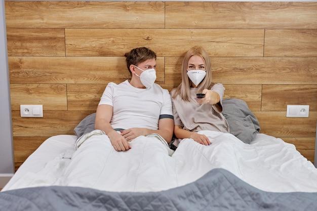 医療用マスクのカップルがコロナウイルス病に苦しんでいる間、テレビを見ながらベッドに座り、女性はリモコンを押してテレビ画面を見ます。検疫、自己隔離の間、家にいる