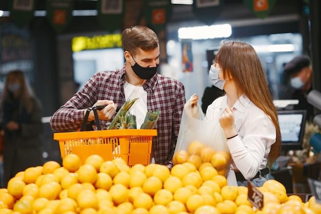 슈퍼마켓에서 의료 보호 마스크에 커플입니다.