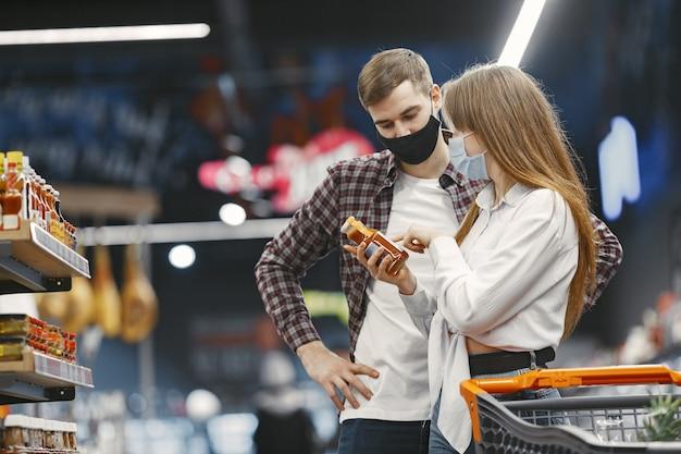 スーパーマーケットの医療用保護マスクのカップル。