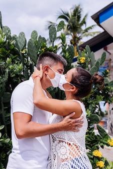Пара в медицинских белых масках на отдыхе стоит возле отеля и целуется