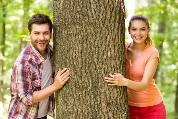 자연 속에서 커플입니다. 공원에 서 있는 동안 나무 밖을 내다보고 웃고 있는 아름다운 젊은 부부
