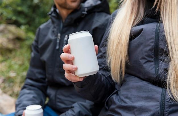 自然の中でカップルが飲み物を飲むクローズアップ