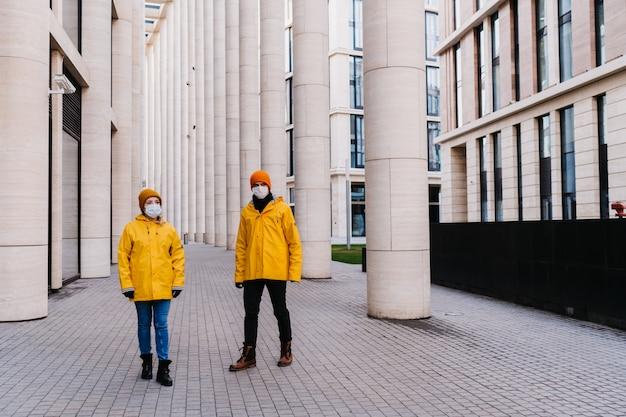 パンデミック状況のため、検疫中に空の街を歩く黄色のウインドブレーカーを身に着けている防護マスクのカップル。 covid-19ウイルスのコンセプト。