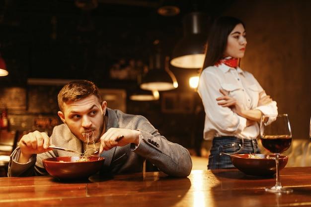 喧嘩中のカップル、男はバーカウンター、恋愛関係、ペーストと赤ワインでディナーを食べる。パブの恋人、ナイトクラブの夫と妻