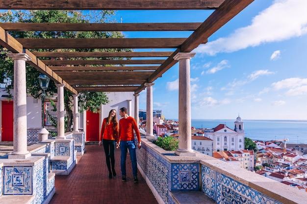 街と海を見下ろす展望台の上を歩く赤いセーターのカップル。木造建築とポルトガルのタイル。