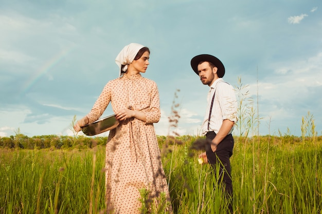 フィールドで田舎の服を着たカップル