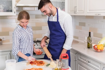 Couple in shirts cooking pizza in kitchen
