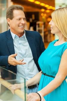 쇼핑몰에서 커플입니다. 쇼핑몰에 서있는 동안 서로 이야기하는 아름다운 성숙한 부부