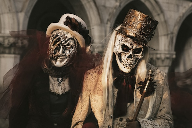 Пара в костюмах скелетов на карнавале в венеции. празднование хэллоуина