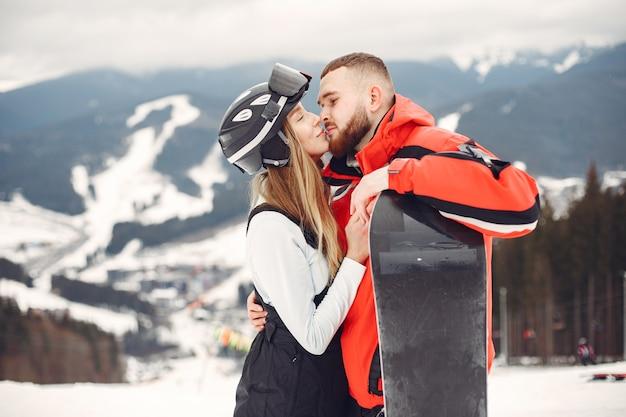 スノーボードスーツのカップル。地平線上にスノーボードを手にした山でスポーツをする人々。スポーツの概念