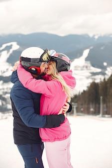 スポーツ服を着たカップル。山で冬休みを過ごす人々
